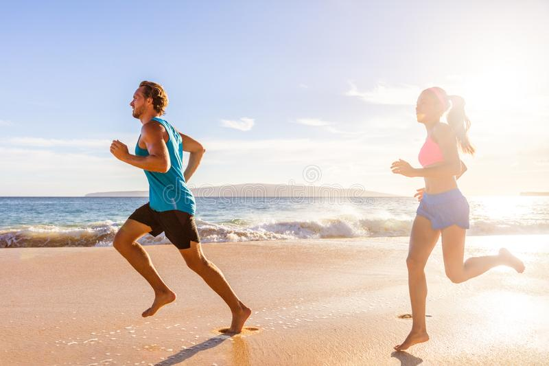 Jogging couple morning beach run healthy lifestyle. Active people training cardio workout together running barefoot in summer. Outdoors royalty free stock photo