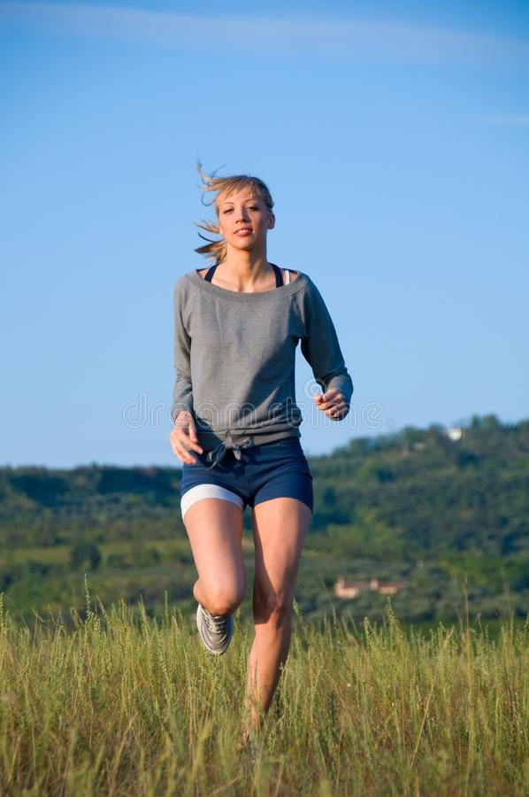 Jogging in a hilly meadow royalty free stock photography