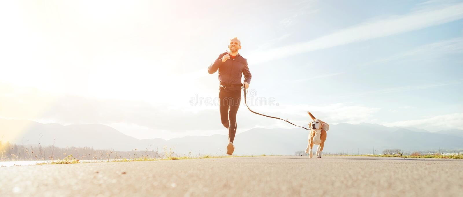 Jogging man with his dog in the morning. Active healthy lifestyle concept image stock image