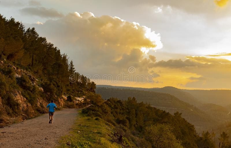 Jogging in the Mountains in the Golden Hour. A jogger on a nature trail, in the mountains near Jerusalem, Israel, in the golden hour before sunset royalty free stock photos