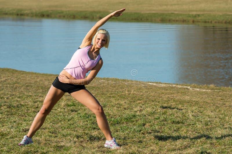 jogging outdoors протягивать детенышей женщины стоковая фотография rf