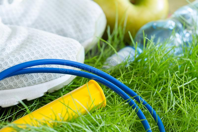Jogging and sport active livestyle concept with sneakers and healthy food outdoor on grass. Closeup stock photography