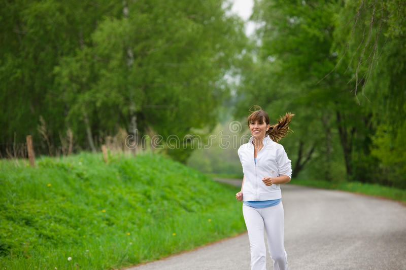 Download Jogging - Sportive Woman Running On Road In Nature Stock Photo - Image: 14430272