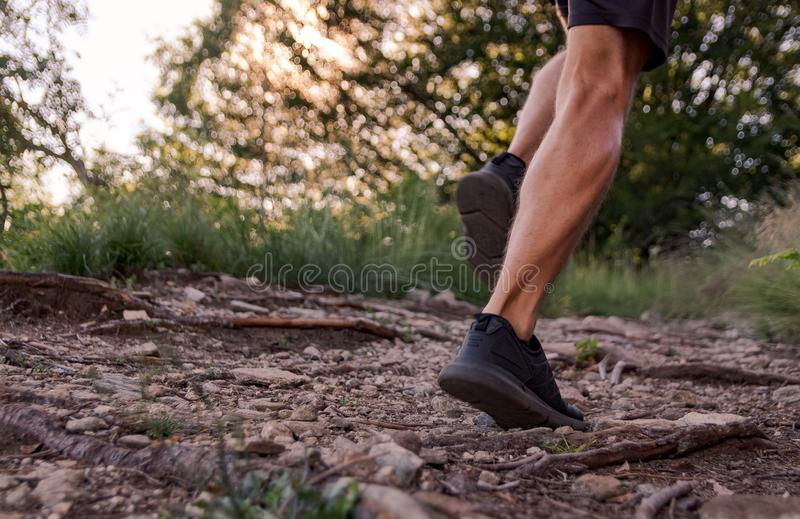 Man legs running on trail in the mountains royalty free stock images