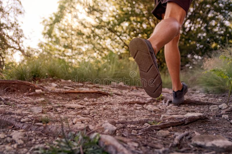 Man legs running on trail in the mountains stock photography