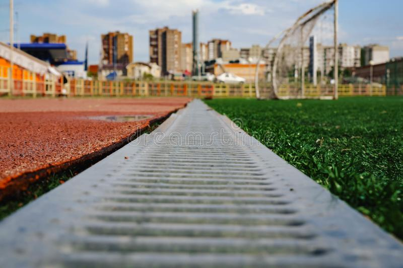jogging track with metal grating and green grass royalty free stock photography