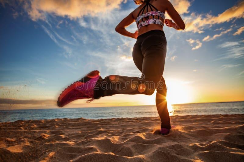 Jogginr apto de la muchacha de la playa de la puesta del sol en la arena contra fondo de la puesta del sol fotografía de archivo