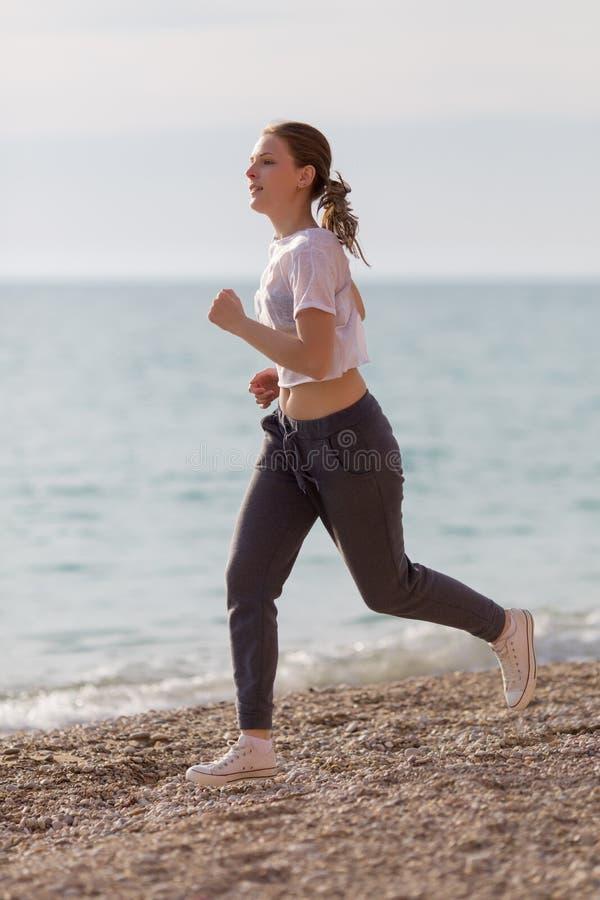 joggle Dziewczyna bieg przeciw morzu w wieczór czasie zdjęcie stock