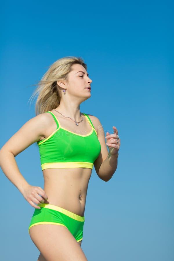joggle Młoda sportsmenka biega outdoors w zielonym sportswear zdjęcia stock