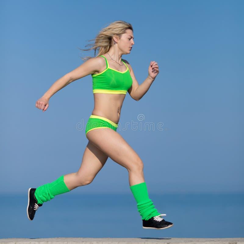 joggle Młoda sportsmenka w zielonym sportswear bieg fotografia royalty free