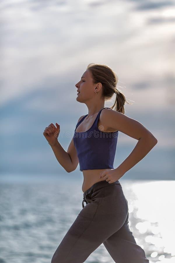joggle Sportsmenka bieg przeciw morzu w wieczór czasie zdjęcie stock