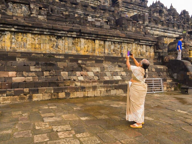JOGJA, INDONÉSIE - 12 août, 2O17 : Femme non identifiée prenant des photos d'un mur avec le soulagement de Bas, temple de Borobud photographie stock