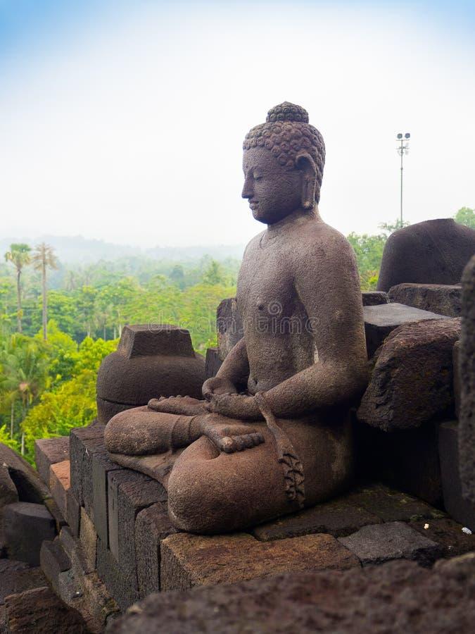 JOGJA, INDONESIA - AUGUST 12, 2O17: Close up of buddha statue and stupa at Borobudur Buddhist temple Candi Borobudur. Built in 9th century, cataloged as stock photo