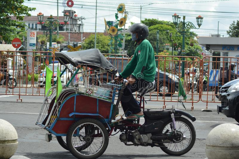 Jogjakarta, Indonesi? march23, 2019: rachitische riksja die elke straathoek in Malioboro Yogyakarta onderzoeken stock fotografie