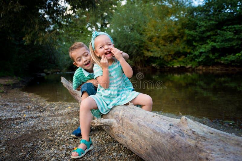 Jogo adorável parvo por um rio, conceito dos irmãos do verão fora imagens de stock royalty free