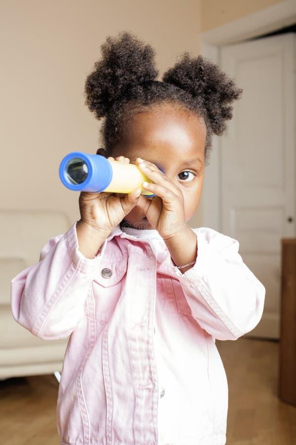 Jogo afro-americano doce bonito pequeno da menina feliz com brinquedos em casa, conceito das crianças do estilo de vida fotografia de stock royalty free
