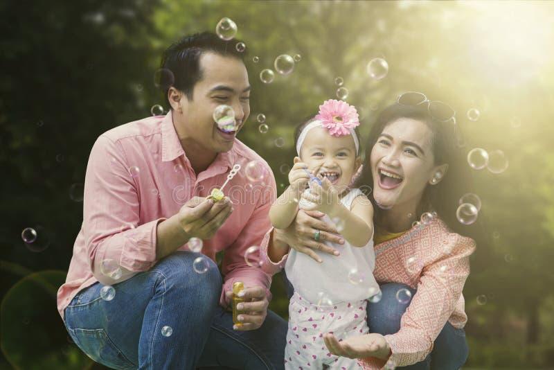 Jogo alegre da família com bolhas de sabão foto de stock