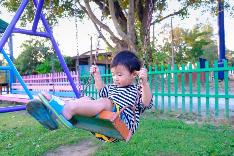 Jogo asiático novo do menino um ferro que balança no campo de jogos sob foto de stock royalty free