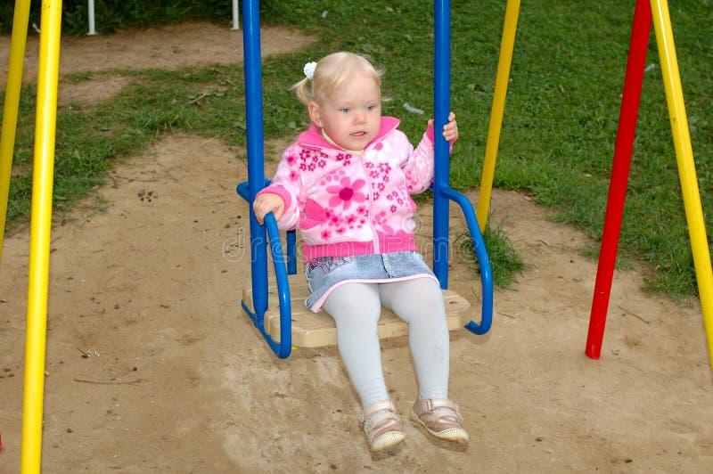 Jogo bonito da menina no campo de jogos no parque. fotografia de stock royalty free