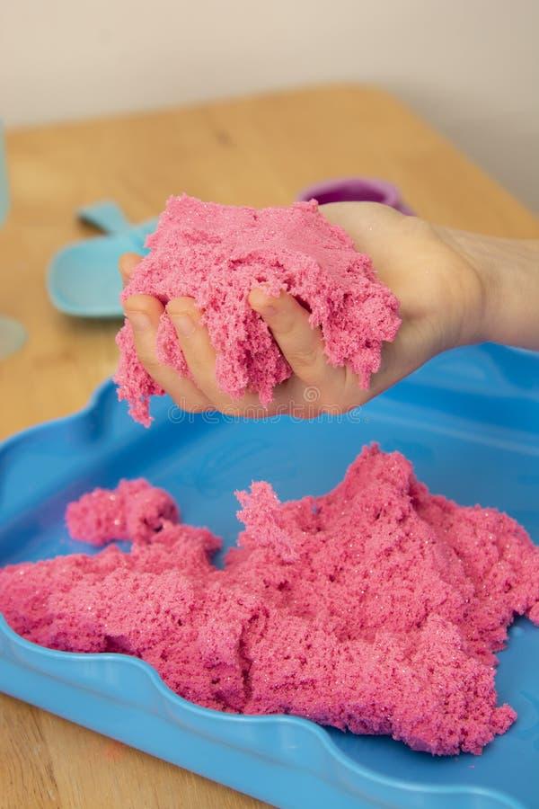 Jogo criativo para crianças Educação e Parenting Crianças que jogam com a areia cor-de-rosa do kinetik foto de stock