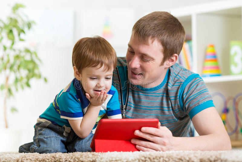 Jogo da criança do pai e do filho com tablet pc imagens de stock royalty free