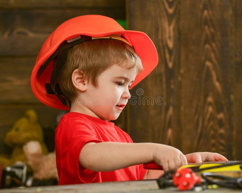 Jogo da criança na tabela com ferramentas Conceito Handcrafting Criança no jogo bonito do capacete como o construtor ou o reparad fotografia de stock royalty free