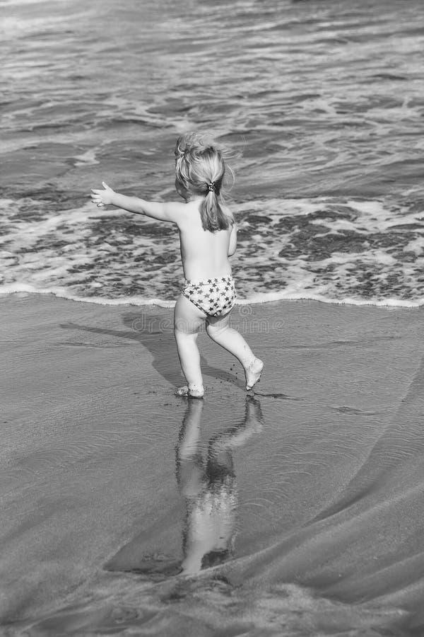 Jogo da criança O bebê alegre bonito corre na areia molhada ao longo do mar foto de stock royalty free