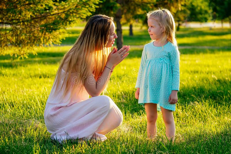 Jogo da etiqueta menina loira, bonita, de vestido azul, com uma linda mãe de cabelos longos, divertindo-se e brincando de surpres foto de stock