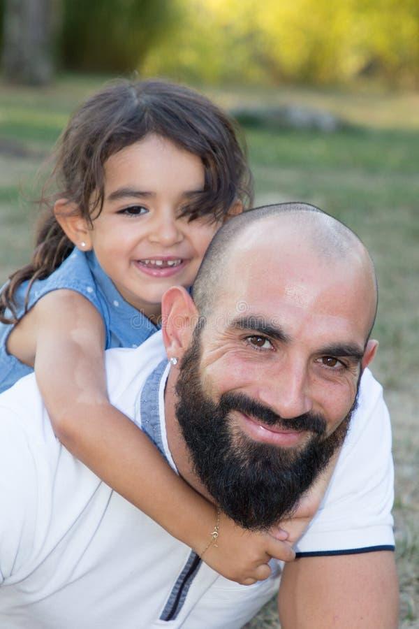 Jogo da filha da criança com o pai farpado no parque da casa do jardim fotografia de stock royalty free