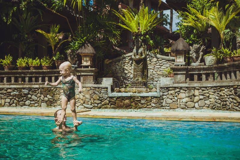 Jogo da mãe do moderno com sua criança bonita na piscina, Bali fotos de stock