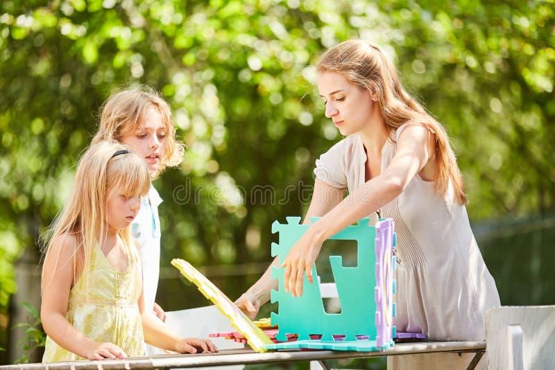 Jogo da mãe e de crianças com partes do enigma foto de stock