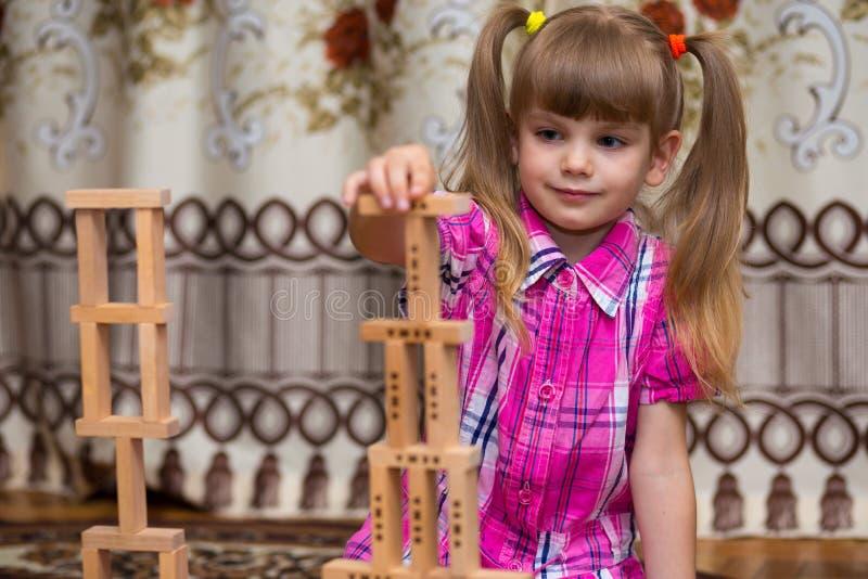 Jogo da menina com blocos de madeira imagem de stock
