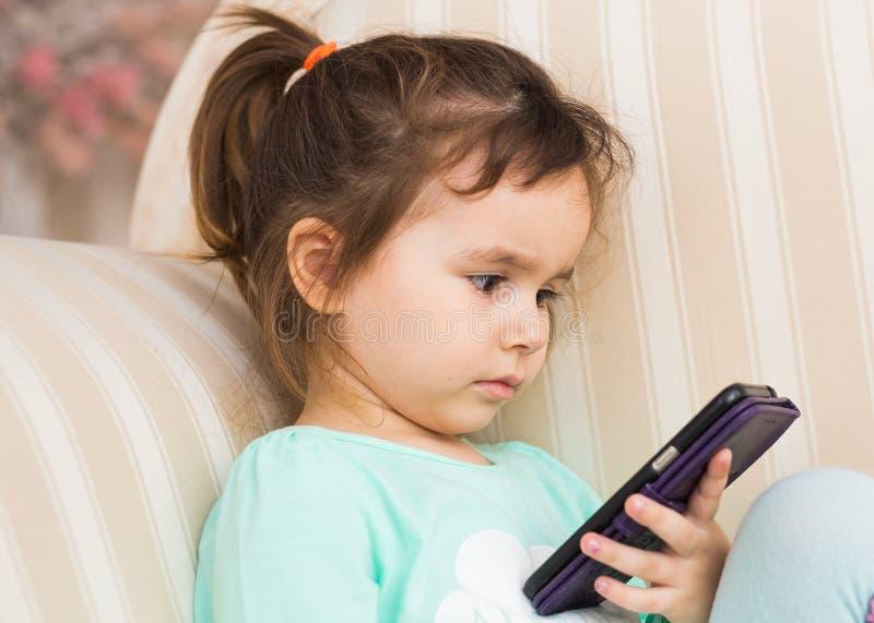 Jogo da menina da criança pequena no smartphone em casa fotografia de stock royalty free