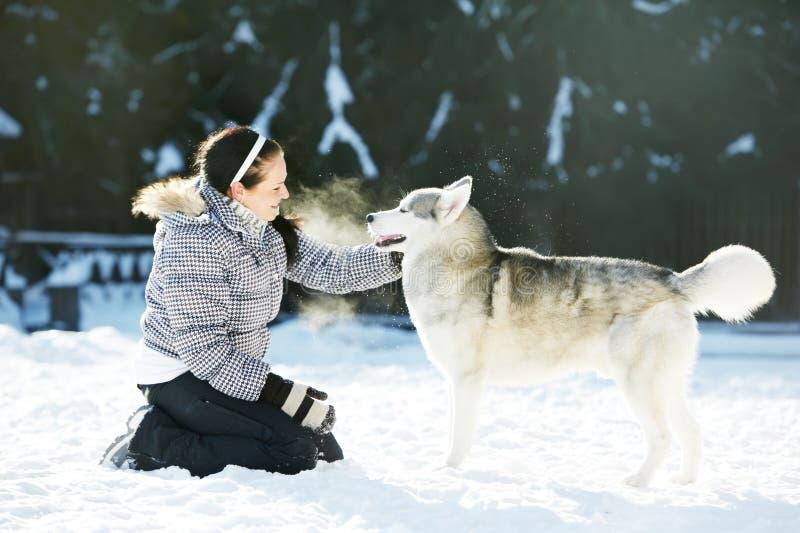 Jogo da mulher com o cão do cão de puxar trenós siberian no inverno foto de stock
