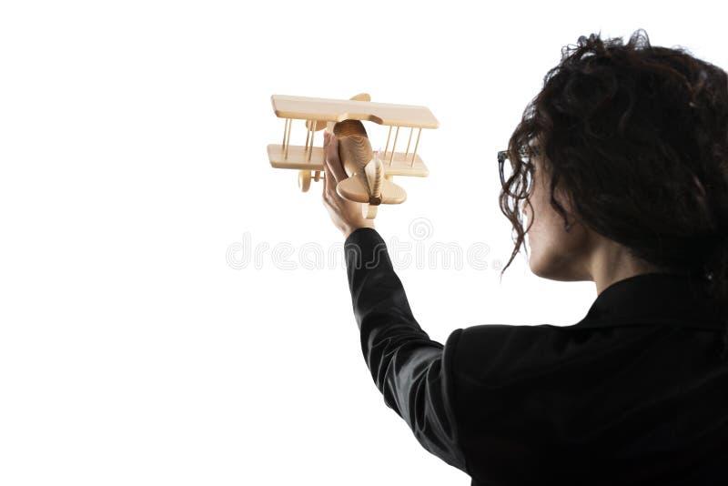 Jogo da mulher de neg?cios com um avi?o do brinquedo Conceito da partida e do sucesso comercial da empresa Isolado no fundo branc fotografia de stock