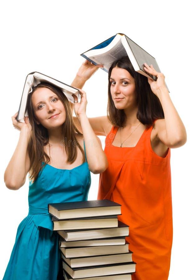 Jogo da mulher do estudante de dois jovens com livros fotos de stock royalty free