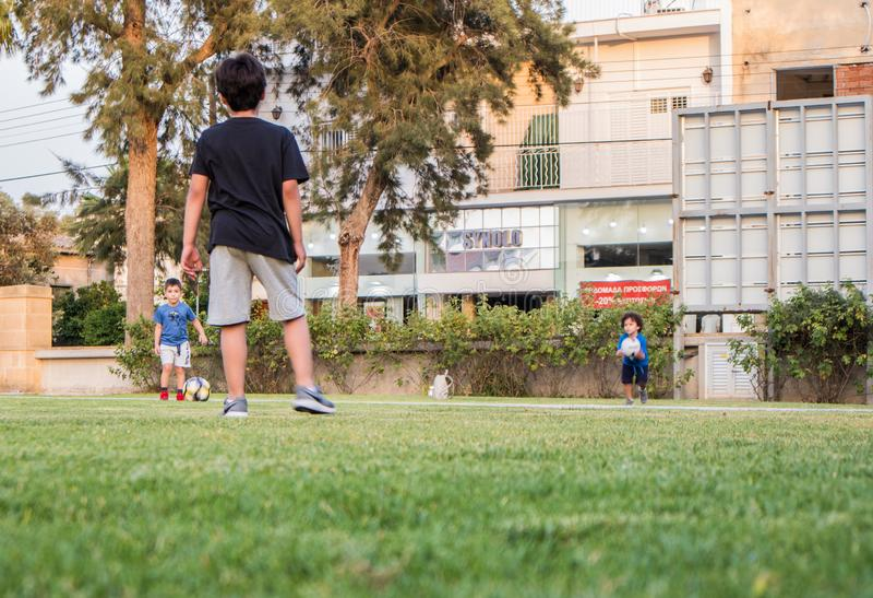 Jogo das crianças footbal na grama verde, em um jardim da casa imagens de stock royalty free