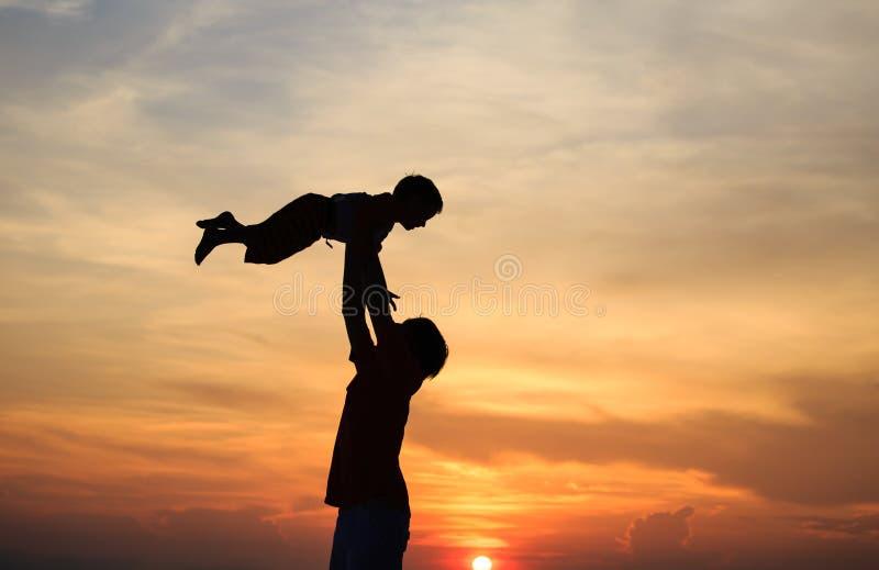 Jogo das silhuetas do pai e do filho no por do sol foto de stock