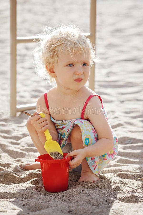 Jogo de assento da menina bonito da criança com areia e brinquedos fora no parque imagem de stock royalty free