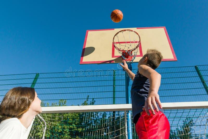 Jogo de basquetebol de Streetball com dois jogadores, adolescentes menina e meninos, manhã no campo de básquete imagem de stock