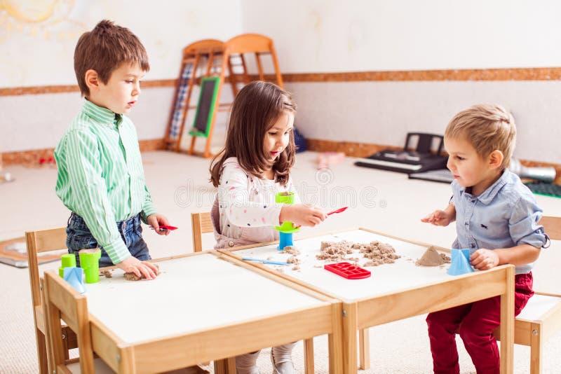 Jogo de crianças com areia cinética fotografia de stock