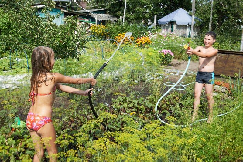 Jogo de crianças com mangueiras de jardim imagem de stock