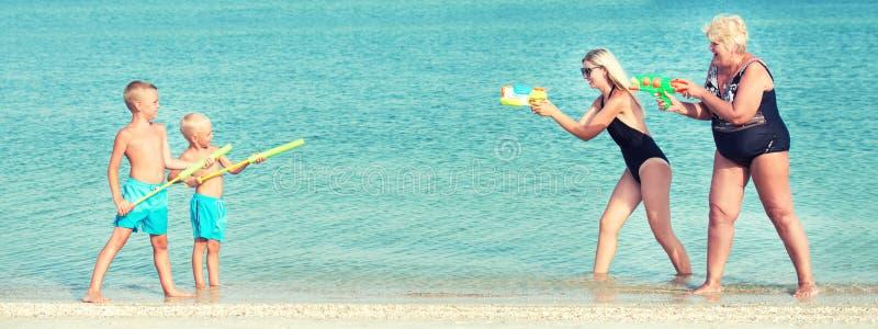 Jogo de crianças com minhas mãe e avó com as pistolas de água na praia Adultos novos foto de stock
