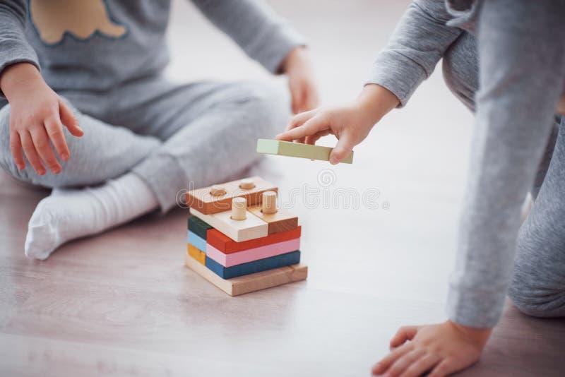 Jogo de crianças com um desenhista do brinquedo no assoalho da sala do ` s das crianças Dois miúdos que jogam com blocos colorido foto de stock royalty free