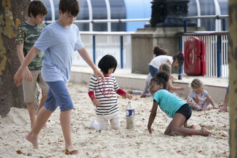 Jogo de crianças na areia no banco sul de Tamisa nas horas de verão imagem de stock royalty free