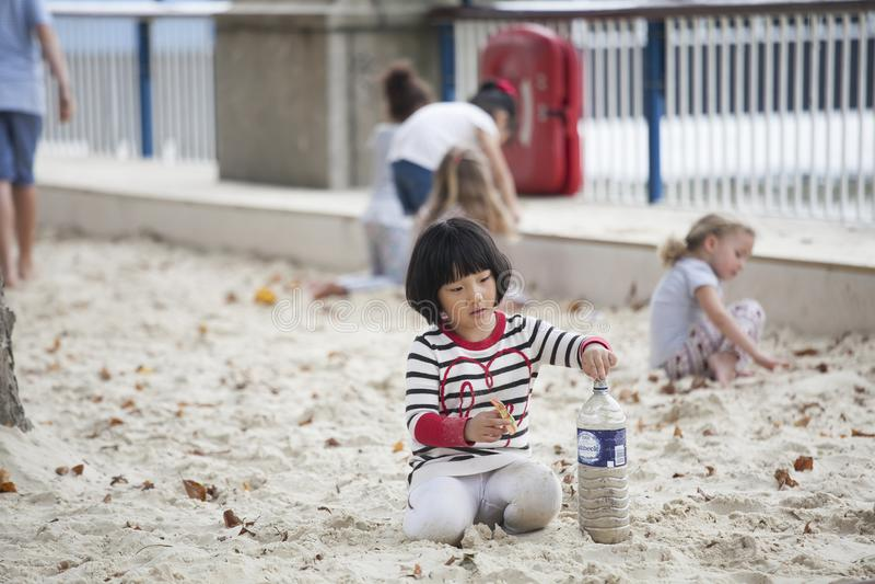 Jogo de crianças na areia no banco sul de Tamisa nas horas de verão foto de stock