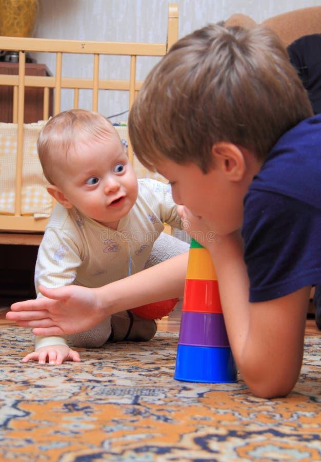 Jogo de dois irmãos em casa imagens de stock royalty free