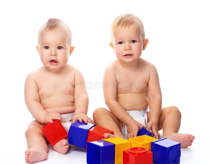 Jogo de duas crianças com tijolos do edifício fotografia de stock royalty free