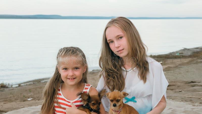 Jogo de duas crianças que persegue na areia na praia imagem de stock royalty free