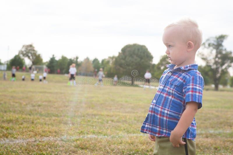 Jogo de futebol de observação da juventude da criança imagem de stock royalty free